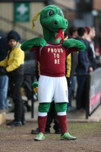 NOTTINGHAM, ENGLAND - NOVEMBER 21: Northampton Town mascot Clarence the Dragon displays a proud to be slogan prior to the Sky Bet League Two match between Notts County and Northampton Town at Meadow Lane on November 21, 2015 in Nottingham, England. (Photo by Pete Norton/Getty Images)